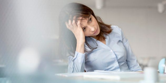 Tired businesswoman with head in hands looking