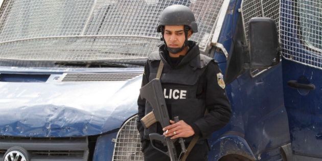 An armed Tunisian police officer, stands guard at the morgue of the Charles Nicolle hospital in Tunis,...