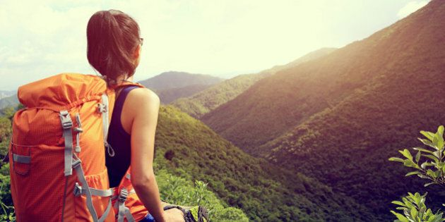 woman backpacker enjoy the view at mountain peak