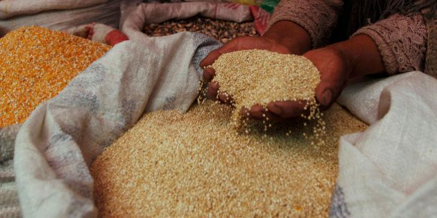 A woman shows her quinoa grain for sale at a market in La Paz, Bolivia, Friday March 2, 2012.  Bolivian authorities say at least 30 people have been injured in a fight between two communities over land for growing quinoa, the Andean
