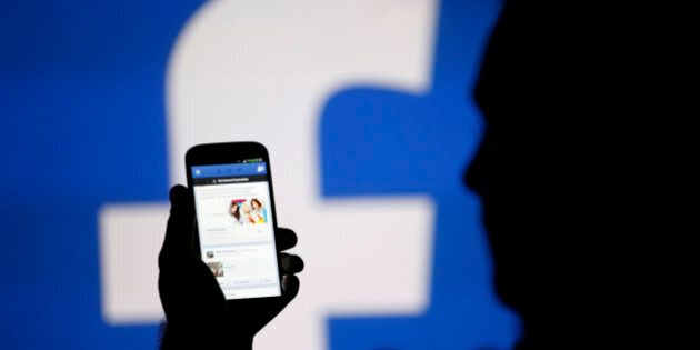 A man is silhouetted against a video screen with an Facebook logo as he poses with an Samsung S4 smartphone...