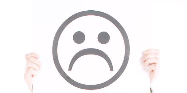 Two people holding frowning and smiley face