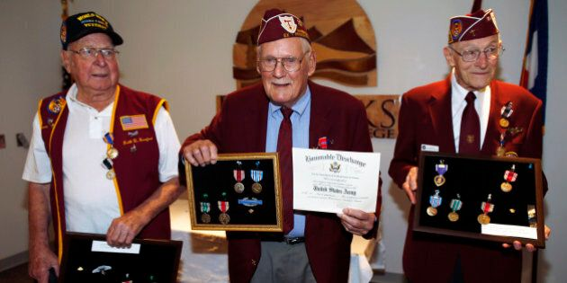 John Pederson, center, holds up his medals as well as his honorable discharge certificate as fellow veterans...