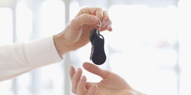 Car salesman handing keys to