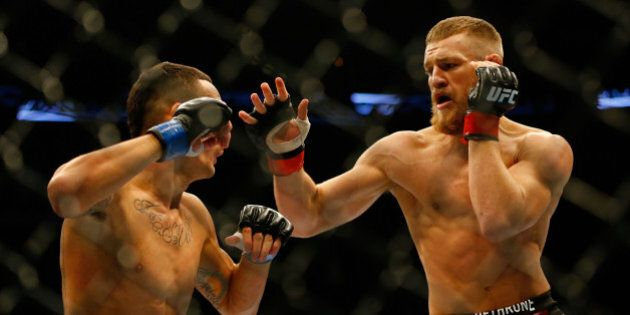 BOSTON, MA - AUGUST 17: Conor McGregor punches Max Holloway in their featherweight bout at TD Garden...