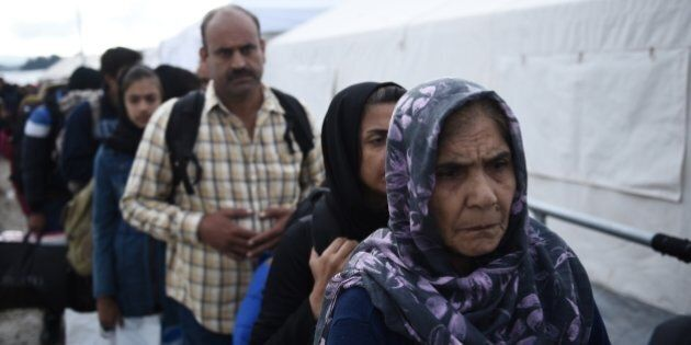 An elderly Afghan woman, right, waits in a queue to be allowed to cross from the northern Greek village of Idomeni to southern Macedonia, Friday, Oct. 9, 2015. Very few of those arriving in Greece want to stay in the financially stricken country, instead moving north through the Balkans to more prosperous European Union countries such as Germany, Austria and Sweden.(AP Photo/Giannis Papanikos)