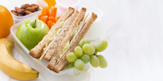 school lunch with sandwiches and fruit on white background,