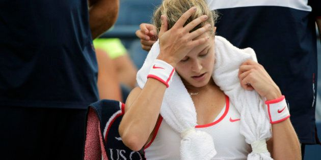 Eugenie Bouchard, of Canada, takes a break between games against Dominika Cibulkova, of Slovakia, during...