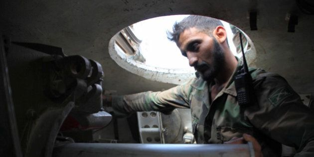 A Syrian soldier is seen inside an army tank on September 4, 2016 at a location on the southern outskirts...