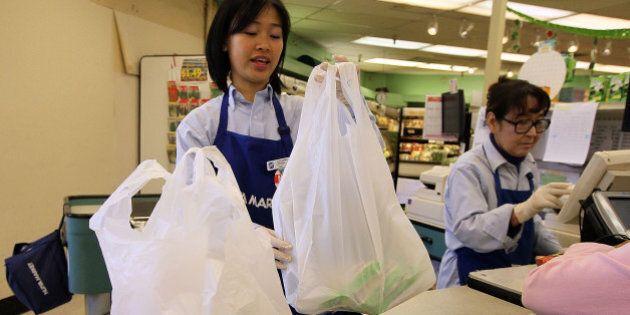 SAN FRANCISCO - JUNE 02: A cashier bags groceries in plastic bags at Nijiya Market June 2, 2010 in San...