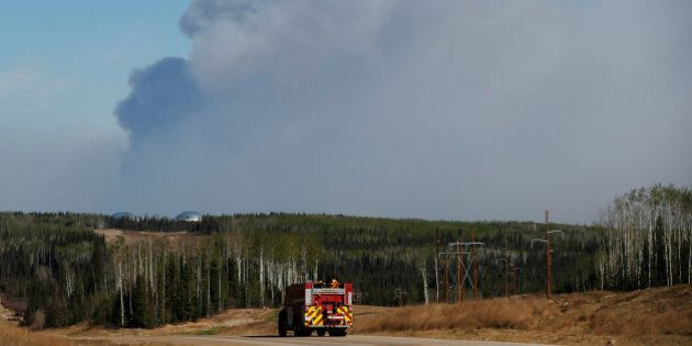 A fire truck drives down a highway in front of the Fort McMurray wildfires in Kinosis, Alberta, Canada,...