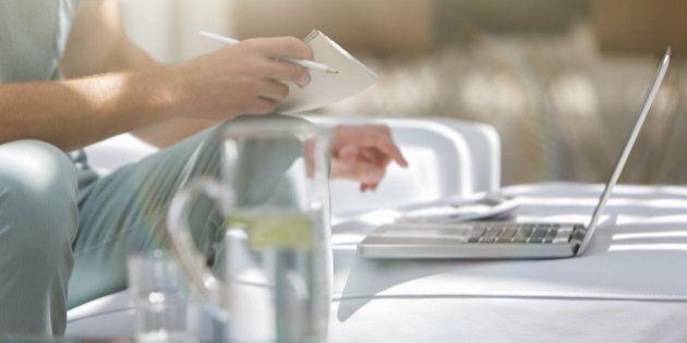 Man paying bills on laptop at coffee