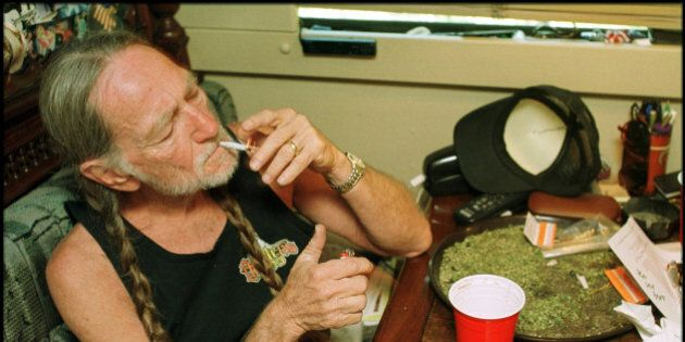 American country singer Willie Nelson takes a drag off a joint while relaxing at his home in Texas, 2000s....