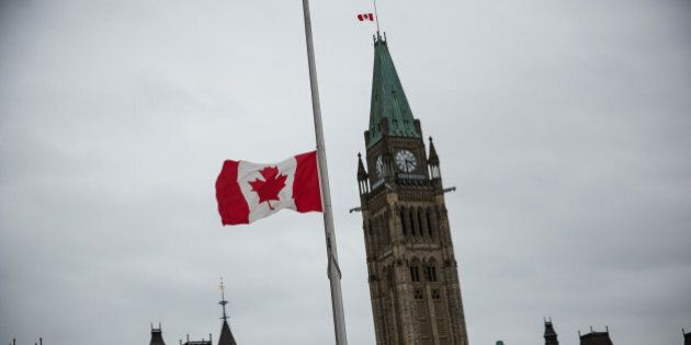 OTTAWA, ON - OCTOBER 23: A flag next to the Canadian Parliament Building is flown at half staff one day...