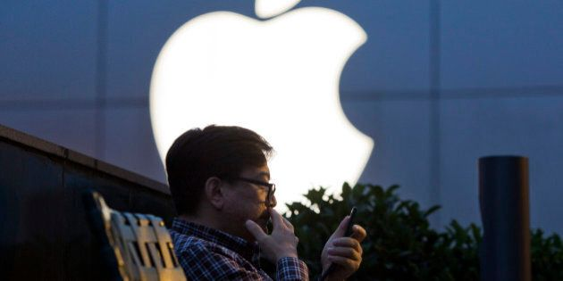 A man uses his mobile phone near a Apple store logo in Beijing, China, Friday, May 13, 2016. Apple Inc....