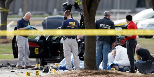 FBI crime scene investigators document the area around two deceased gunmen and their vehicle outside...
