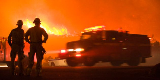 Firefighters stand watch as a fire truck passes while the Jesusita Wildfire burns in Santa Barbara