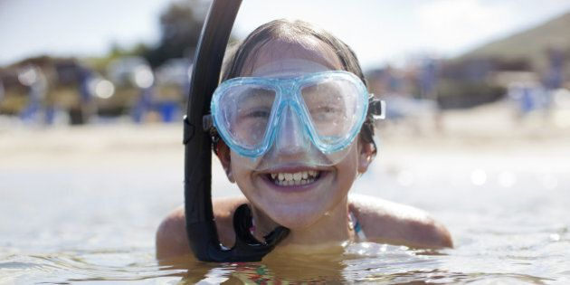 Happy girl wearing snorkel and goggles in