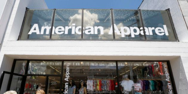 Passers-by walk down the street past the American Apparel store in the Shadyside neighborhood of Pittsburgh...