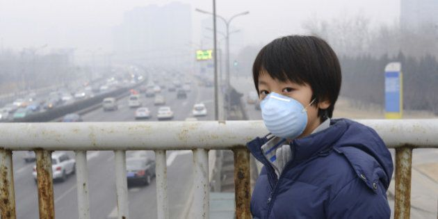 Asian child protects himself against air pollution by wearing mouth