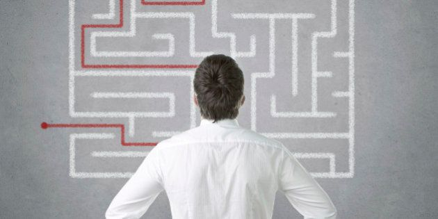 Confused young businessman looking at the labyrinth on the