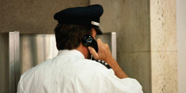 Security guard using telephone, rear