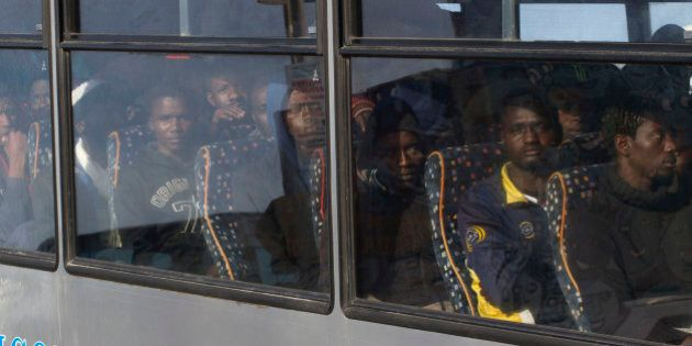 Rescued migrants sit on a bus after disembarking from an Italian Coast Guard ship in the harbor of Lampedusa,...