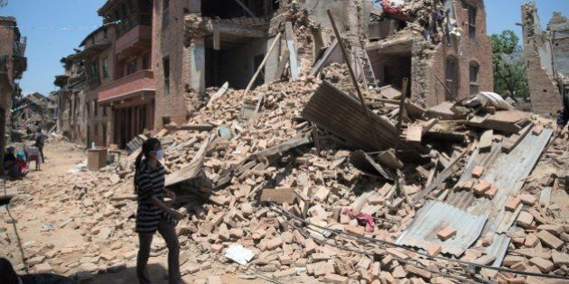 A Nepalese woman walks next to damaged homes in Sankhu town in the Kathmandu Valley on May 3, 2015, following...