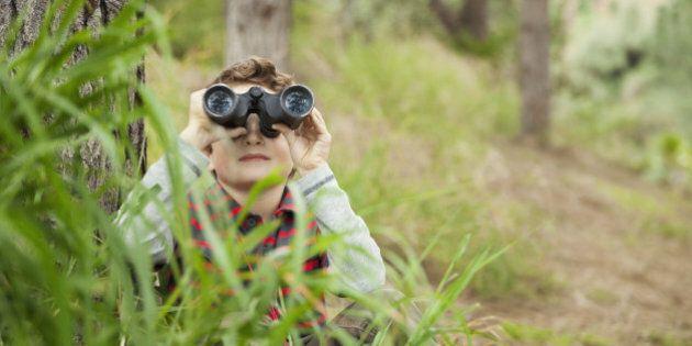 Young boy looking through binoculars in tall