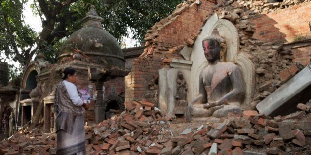 A Nepalese woman offers morning prayers at a temple damaged in last Saturday's earthquake in Bhaktapur,...