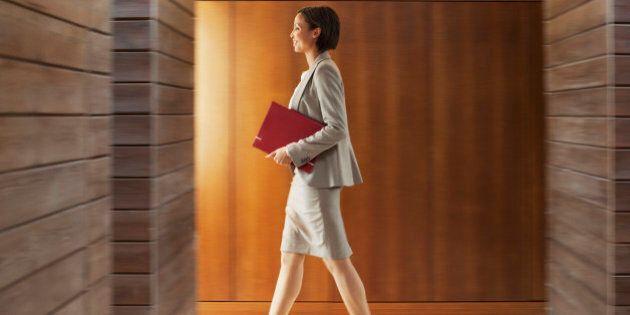 Businesswoman with folder walking in office