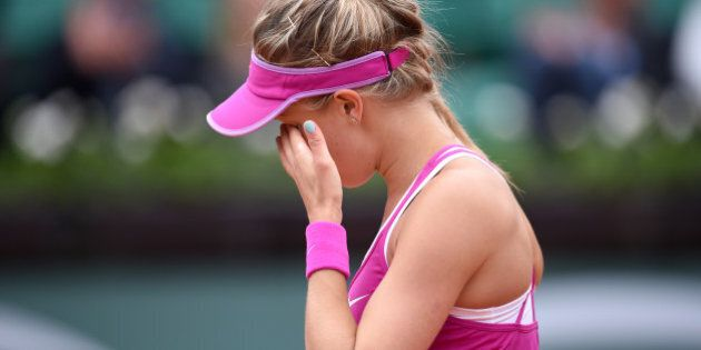 Eugenie Bouchard wipes her face dejected during her 1st round women's singles match against Kristina...