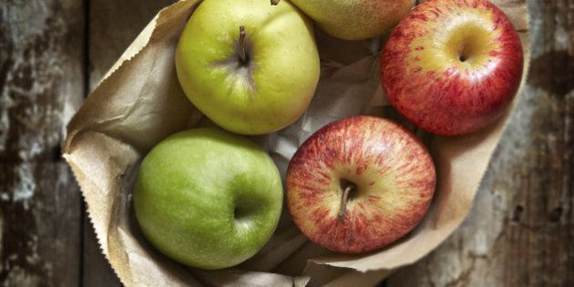 Assorted apples and pears on brown paper and a wooden work surface.