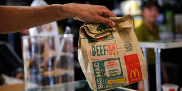 A customer takes a McDonald's Corp. bag of food inside a McDonald's restaurant in Manchester, U.K., on Monday, Aug. 10, 2015. McDonald's Chief Executive Officer Steve Easterbrook predicted a return to growth for the burger chain in the second half of the year, giving investors cause for optimism after another quarter of slumping sales. Photographer: Paul Thomas/Bloomberg via Getty Images