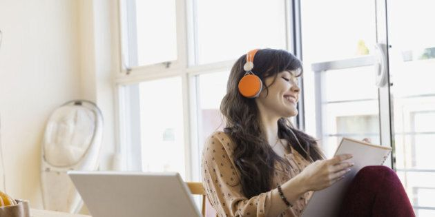 Woman with headphones and notebook at