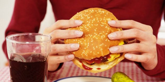 Woman holding cheeseburger, soft drink beside plate, close-up