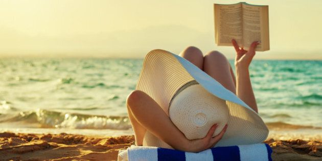 woman lying on beach and reading, sunset time, at the edge of sea, sunhat.photo taken in summer day outdoors.