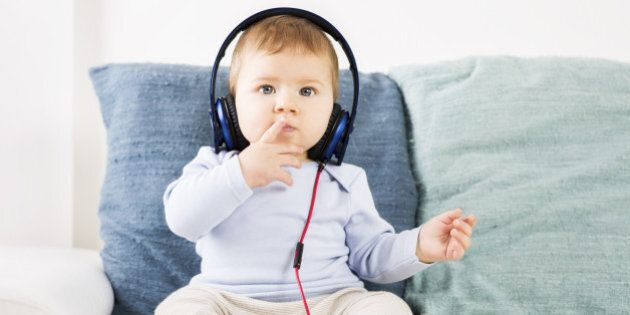 Sweet baby boy sitting on sofa and listening music at headphones while holding one finger in front of his mouth.