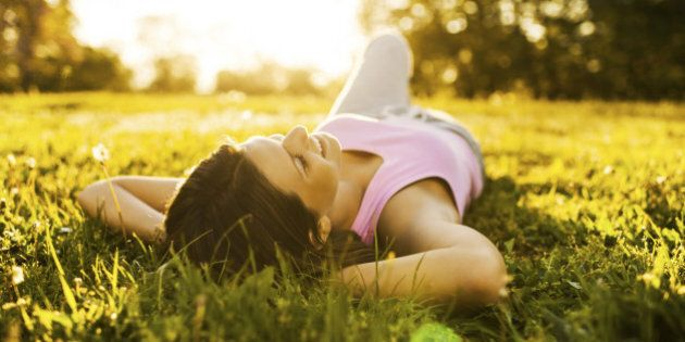 Teenage girl lying on grass with her eyes closed and enjoying the sunset.