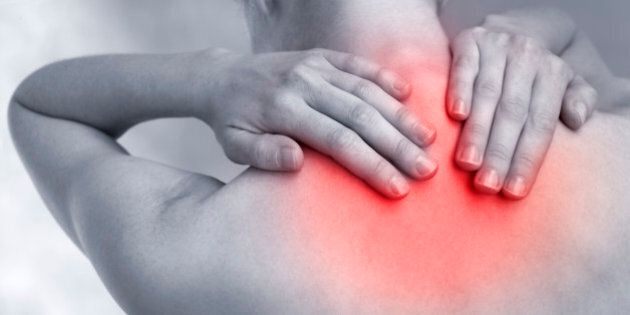Female hands hold the base of the neck between the shoulder blades to relieve pain or tension emphasised by the red tinting