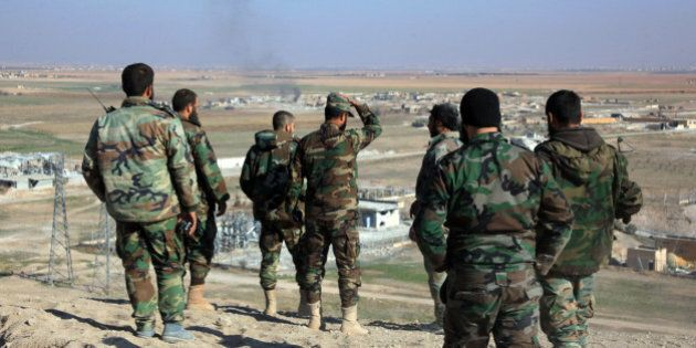 Syrian pro-government fighters look at smoke rising on the horizon following government air strikes on...