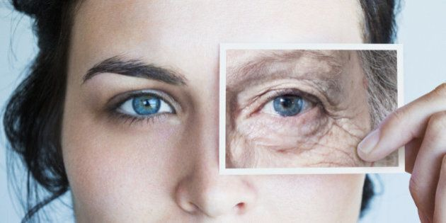 Young woman with photo of aged eye over her