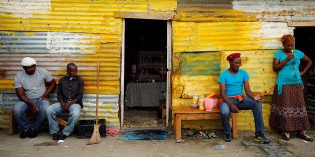 Members of a mining community sit outside a shack in Nkaneng township, Marikana's informal settlement,...