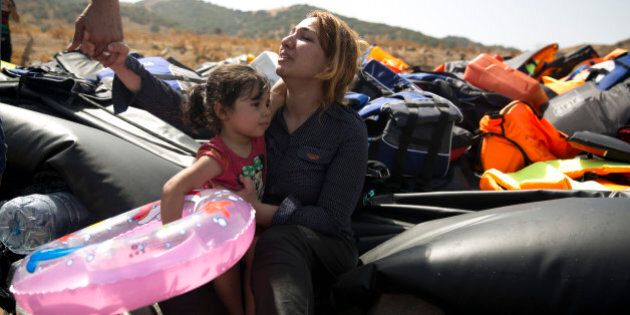 A Syrian family react after arrived with others aboard a dinghy from Turkey, on the island of Lesbos,...