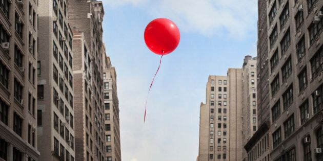 Red balloon floating through city