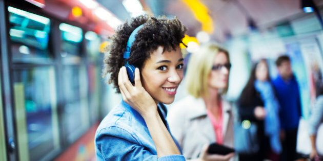 Smiling woman listening to headphones in subway