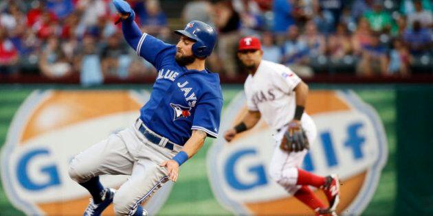 Toronto Blue Jays' Kevin Pillar, left, slides into second on a steal as Texas Rangers second baseman...