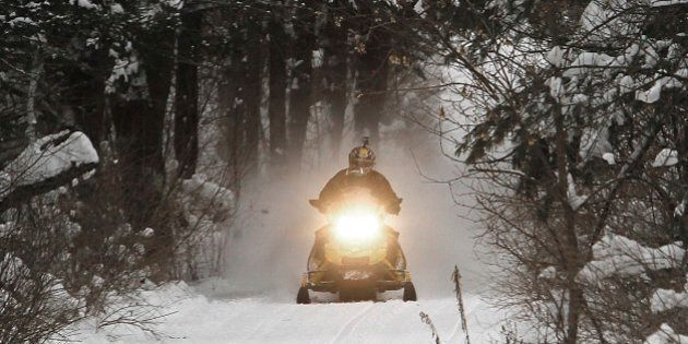 A snowmobile travels a newly-groomed trail on Monday, Dec. 31, 2012 in East Montpelier, Vt. The big snow...