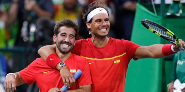 Rafael Nadal, right, and Marc Lopez, of Spain, celebrate after defeating Canada in their men's doubles...