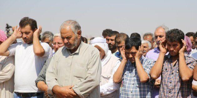 KOBANI, SYRIA - SEPTEMBER 4: Relatives perform prayer during funeral of Syrian children Aylan, 2, his...